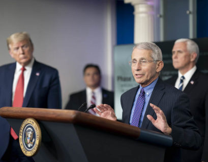 Fauci speaks to the White House press corps on COVID-19 in April 2020, watched by President Donald Trump (left) and Vice President Mike Pence (right)